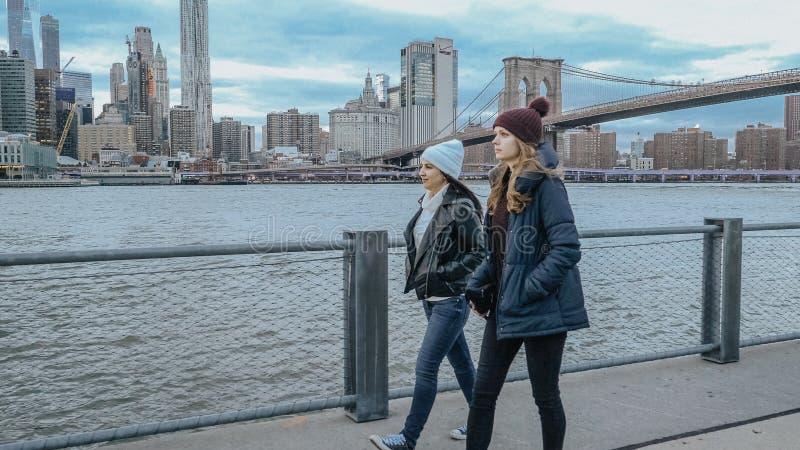 Dwa przyjaciela chodzą wzdłuż zadziwiającego linia horyzontu Manhattan w wieczór obrazy stock