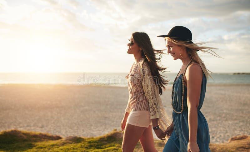 Dwa przyjaciela chodzi na plaży na letnim dniu fotografia stock