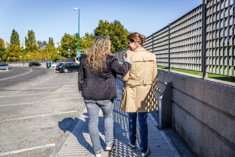 Dwa przyjaciela gawędzą i one uśmiechają się gdy chodzą cicho puszek ulica zdjęcie royalty free