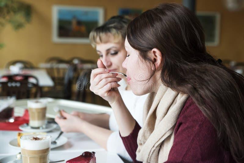 Dwa przyjaciela komunikują z jedzeniem i jedzą tort, napój kawa obraz royalty free