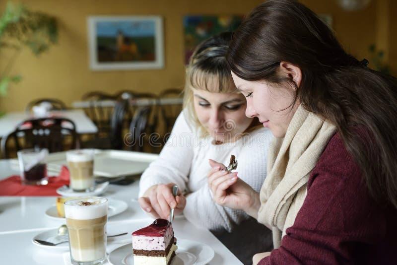 Dwa przyjaciela komunikują z jedzeniem i jedzą tort, napój kawa zdjęcie royalty free