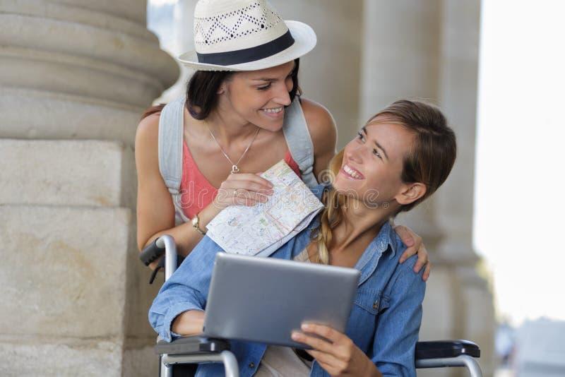 Dwa przyjaciela odwiedza cudzoziemskiego miasta jeden obsiadanie w wózku inwalidzkim zdjęcie royalty free