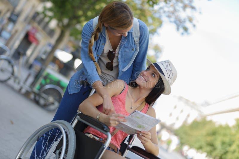 Dwa przyjaciela odwiedza cudzoziemskiego miasta jeden obsiadanie w wózku inwalidzkim fotografia royalty free