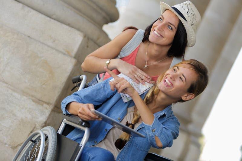 Dwa przyjaciela odwiedza cudzoziemskiego miasta jeden obsiadanie w wózku inwalidzkim zdjęcia stock