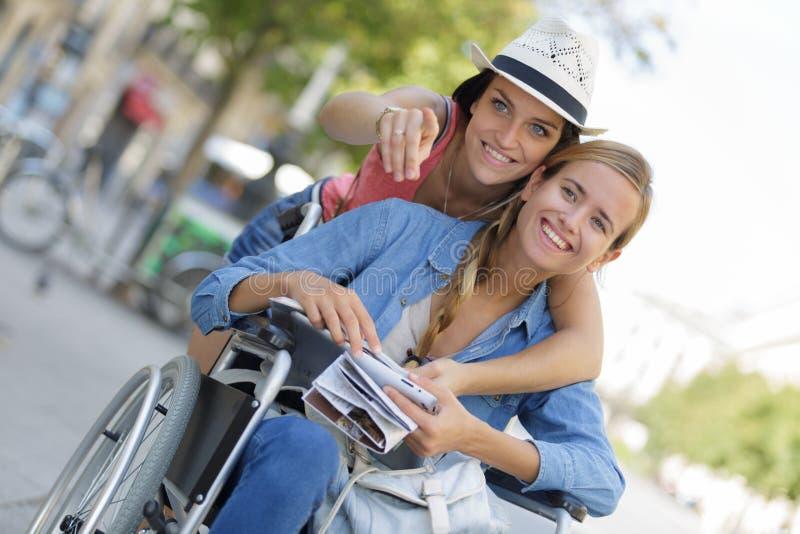 Dwa przyjaciela odwiedza cudzoziemskiego miasta jeden obsiadanie w wózku inwalidzkim obrazy royalty free