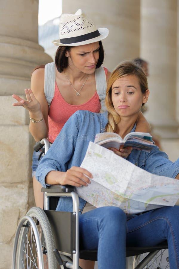 Dwa przyjaciela odwiedza cudzoziemskiego miasta jeden obsiadanie w w?zku inwalidzkim obraz royalty free