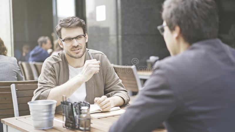 Dwa przyjaciela opowiadają przy stołem kawiarnia outdoors fotografia stock