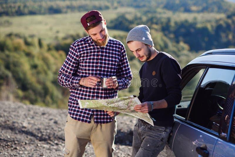 Dwa przyjaciela podróżnika z nakrętką herbaciany znajdować poprawnego sposób i patrzeć papierową mapę Szczęśliwy modnisiów mężczy zdjęcie stock