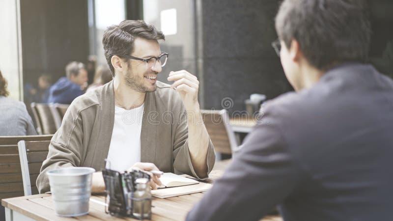 Dwa przyjaciela są roześmiani przy stołem kawiarnia outdoors fotografia stock