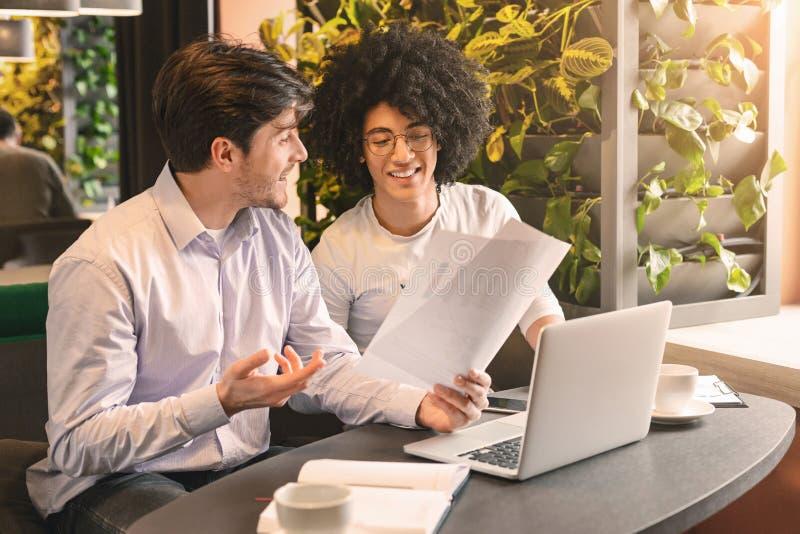 Dwa przystojnego biznesmena dyskutuje znacząco projekt w kawiarni zdjęcie stock