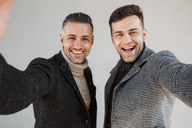 Dwa przystojnego mężczyzny jest ubranym żakiety nad szarym tłem zdjęcia stock