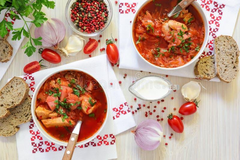 Dwa pucharu Ukraiński borscht na upiększonych pieluchach, chlebie, kwaśnej śmietance, pikantność, cebulach, czosnku, pomidorach i obrazy royalty free