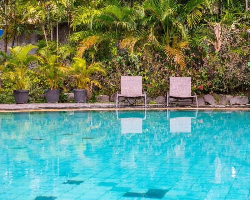 Dwa pustego pokładu krzesła obok ogródu i basen w późnym popołudniu obraz stock