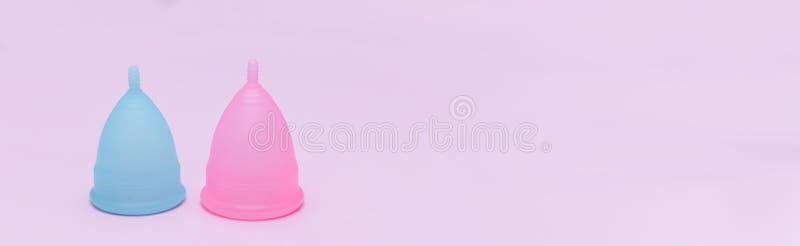 Dwa różowy i błękitnego okresu menstrual filiżanka na różowym tle Pojęcie kobiet zdrowie, higieniczni sposoby ochrona obrazy royalty free