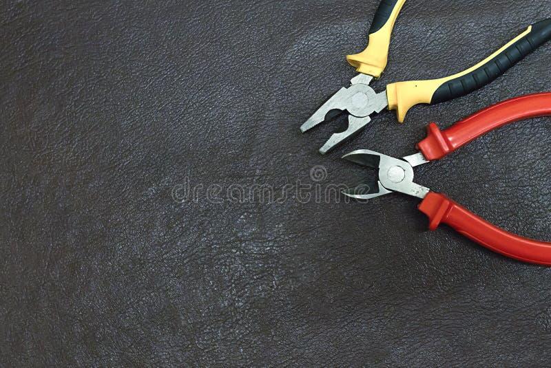 Dwa ręk narzędzi lądzieniec i cążków drutowania projekta elektrycznej remontowej przemysłowej podstawy sieci kopii reklamowej prz obraz stock