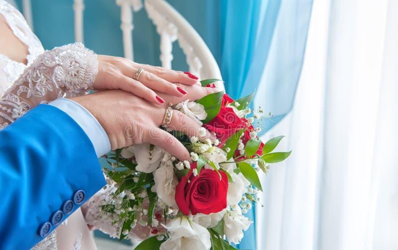 Dwa ręki Bridal w białej sukni i błękitnym kostiumu kłama na kwiatu bukiecie czerwone róże, Horyzontalna rama zdjęcie stock