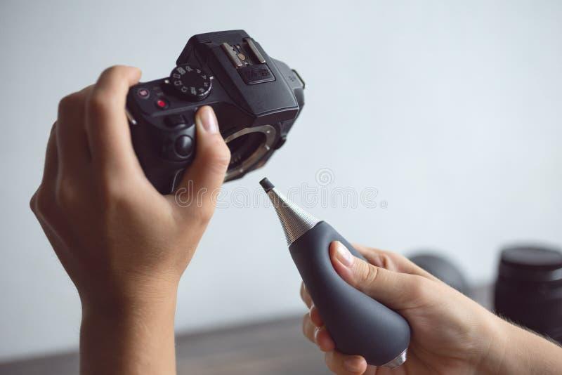 Dwa ręki czyści cyfrowej kamery czujnika od pyłu z lotniczą dmuchawą obrazy royalty free