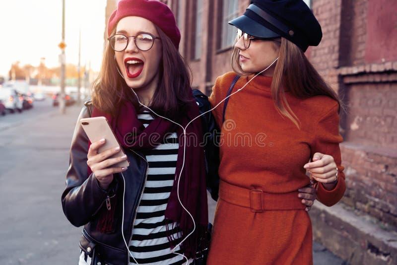 Dwa radosnej młodej dziewczyny tanczy podczas gdy słuchający muzyka na smartphone, miasto plenerowy zdjęcia royalty free