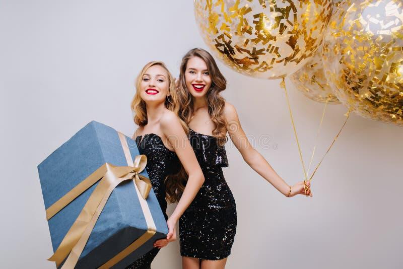 Dwa radosnej modnej młodej kobiety świętuje przyjęcia urodzinowego na białym tle w luksusowych czarnych sukniach dziecka ojca zab obraz royalty free