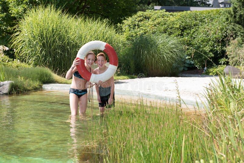 Dwa redhaired dzieciaka w basenie bawić się z bezpieczeństwem dzwonią zdjęcie royalty free