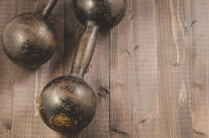 Dwa rocznika dumbbells/Dwa rocznika dumbbells na czerni drewnianym zdjęcie stock