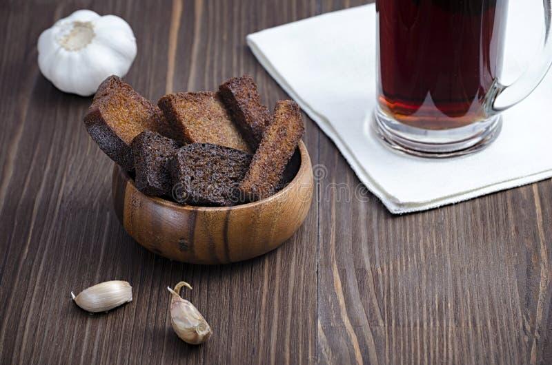 Dwa rodzaju smażący chleb w drewnianym talerzu z czosnkiem i napojem w szkle na drewnianym tle obraz royalty free
