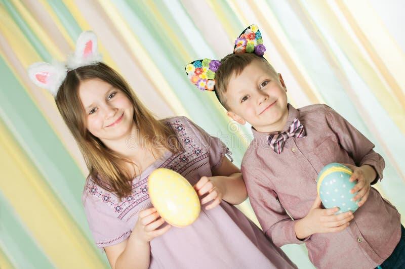 Dwa rodzeństwa stoi z Wielkanocnymi jajkami w ich rękach fotografia royalty free