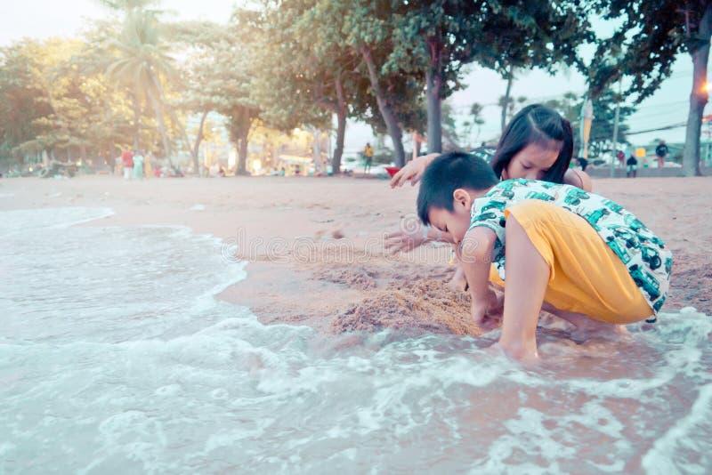 Dwa rodze?stwa dziecka bawi? si? z fal? i piaskiem w Pattaya Wyrzuca? na brzeg Tajlandia obrazy stock