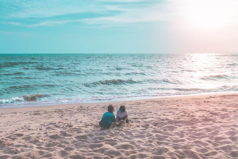 Dwa rodze?stwa dziecka bawi? si? z fal? i piaskiem w Pattaya Wyrzuca? na brzeg Tajlandia fotografia royalty free