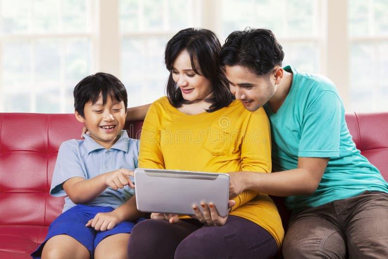Dwa rodzica i ich syn używa pastylkę fotografia royalty free