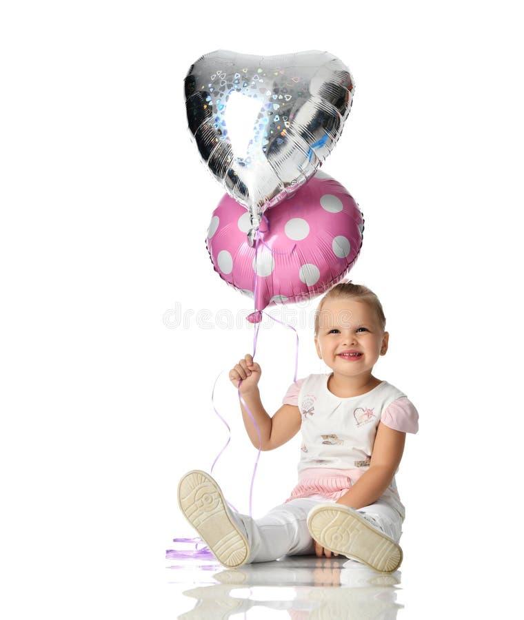 Dwa roku dziewczyna berbecia dzieciaka siedzi odświętność odizolowywającą na bielu z balonami obrazy royalty free