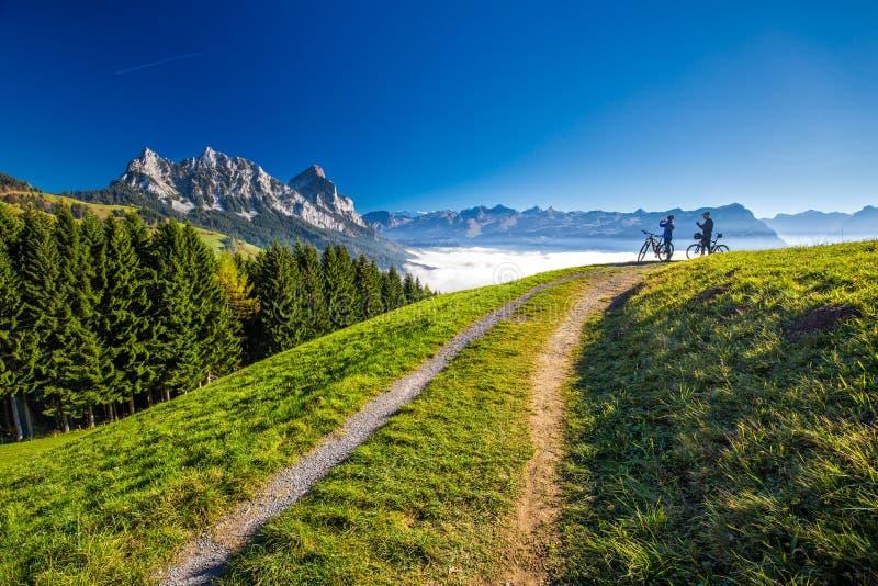 Dwa rowerzysty patrzeje Mythen osiągają szczyt w Szwajcarskich Alps fotografia stock