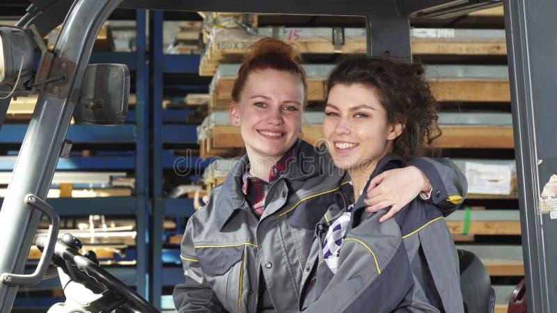 Dwa rozochoconego żeńskiego pracownika fabrycznego ściska ono uśmiecha się szczęśliwie kamera obraz royalty free
