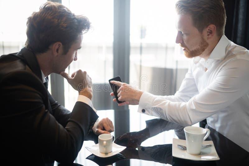 Dwa rozochoconego ludzie biznesu dyskutuje co? i jeden one wskazuje wisz?c? ozdob? w formalwear obrazy stock