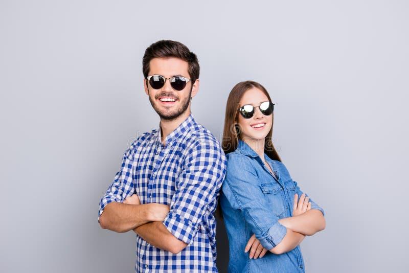 Dwa rozochoconego młodego kochanka są przyglądający w kamerze, będący ubranym eleganckich okulary przeciwsłonecznych i uśmiech, w obrazy royalty free