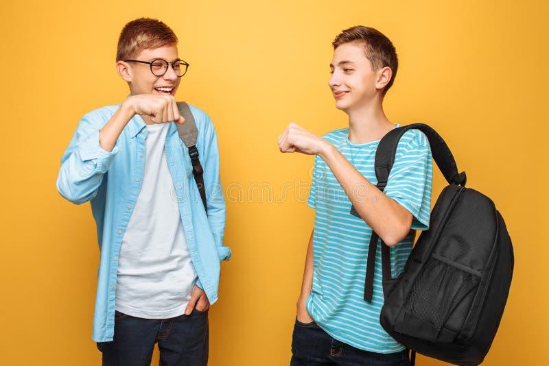 Dwa rozochoconego nastolatka, faceci witają each inny na żółtym tle, zdjęcia royalty free