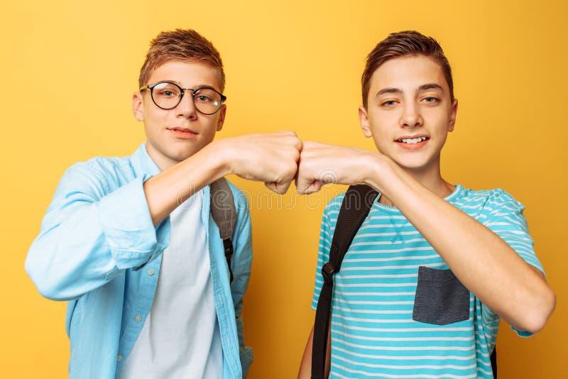 Dwa rozochoconego nastolatka, faceci witają each inny na żółtym tle, obraz royalty free