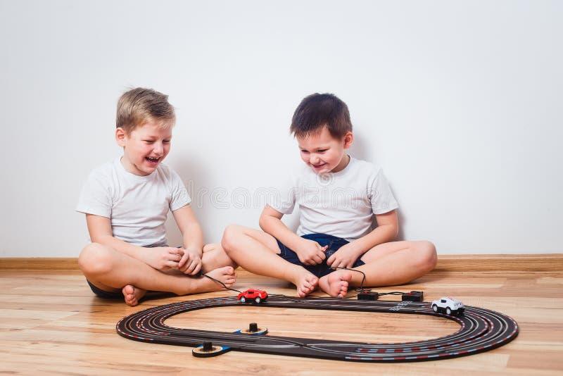 Dwa rozochoconej chłopiec w białych koszulkach zaczynają zabawkarskich samochody zdjęcia royalty free
