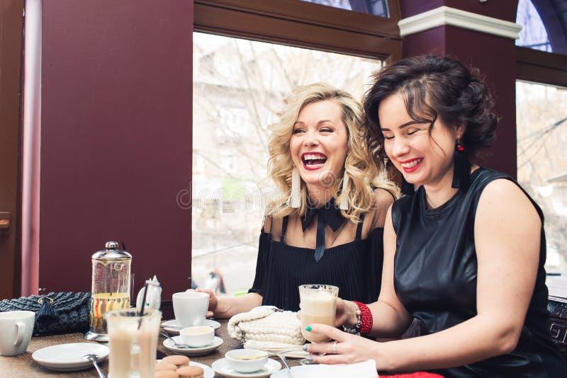 Dwa rozochoconej dziewczyny siedzą przy stołem w kawiarni i napojów napojach obrazy stock
