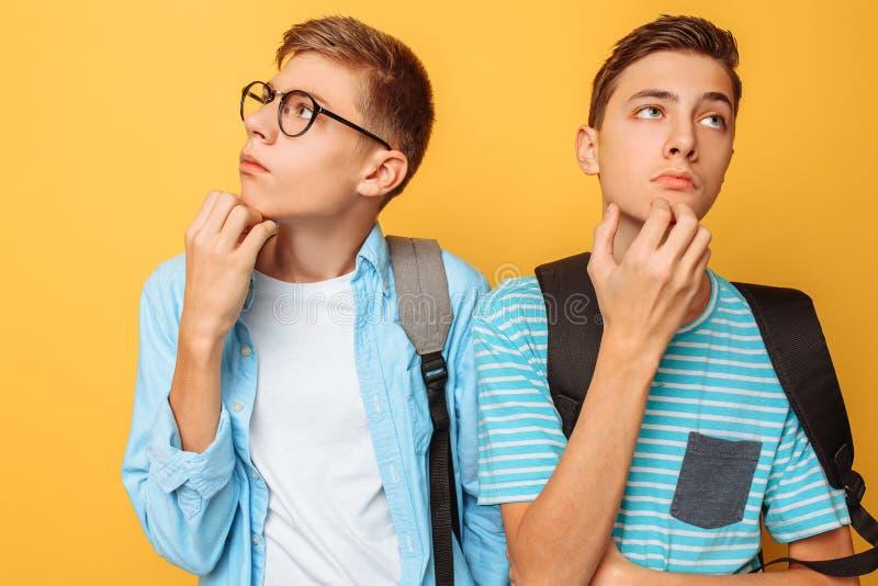 Dwa rozważnego nastolatka, faceci które próbują znajdować prawego rozwiązanie lub robić planom na żółtym tle, obrazy stock