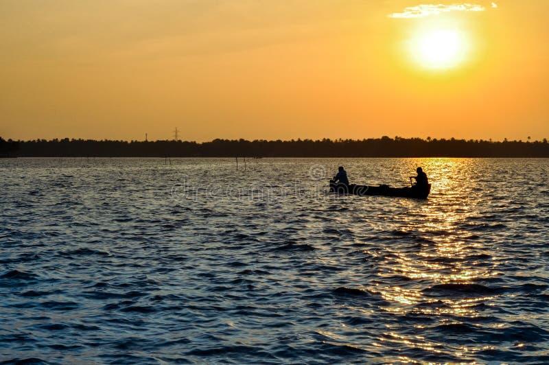 Dwa rybaka wiosłuje małą łódkę w stojących wodach Kerala zdjęcia stock