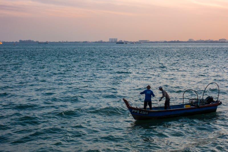Dwa rybaka zbiera sieć rybacką ich mała łódka obrazy royalty free