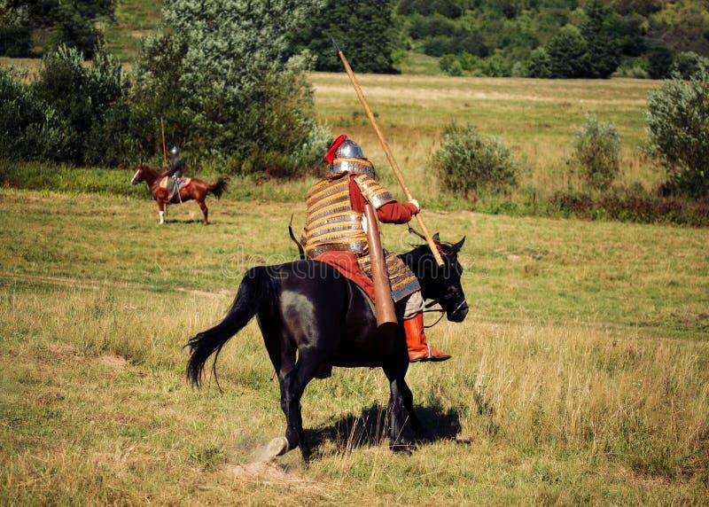 Dwa rycerzy walka Średniowieczni opancerzeni equestrian żołnierze z lancami Jeźdzowie na koniach są w lecie zdjęcie stock