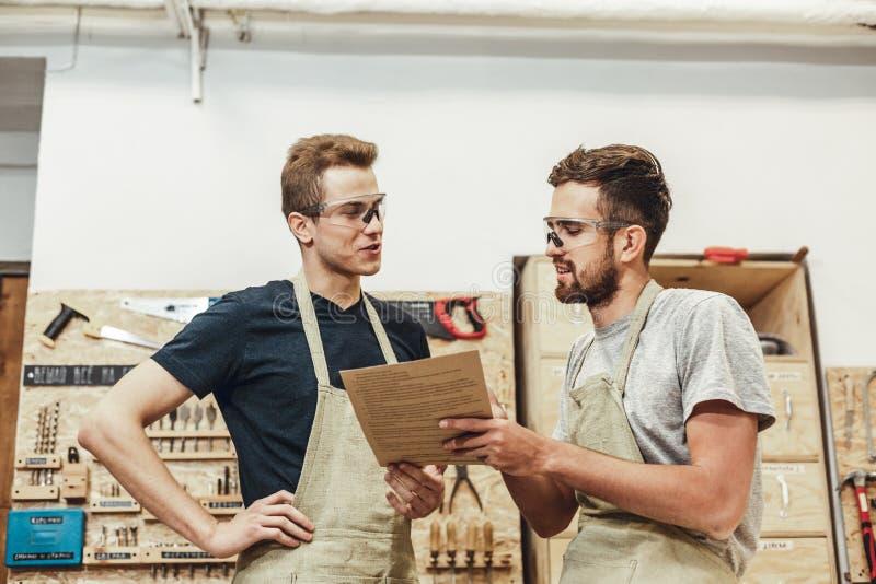 Dwa rzemieślnika dyskutuje papiery zdjęcia stock