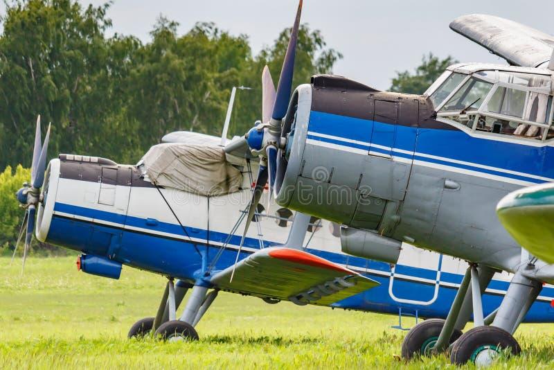 Dwa samolot?w sowiecki biplan Antonov AN-2 parkuj?cy na zielonej trawie lotniska zbli?enie obraz royalty free