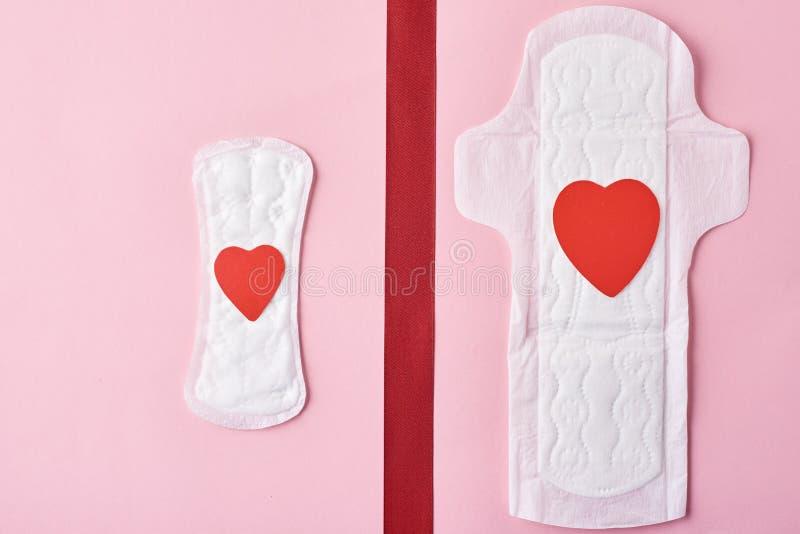 Dwa sanitarnego ochraniacza z sercami i czerwonego faborek na różowym tle obraz stock
