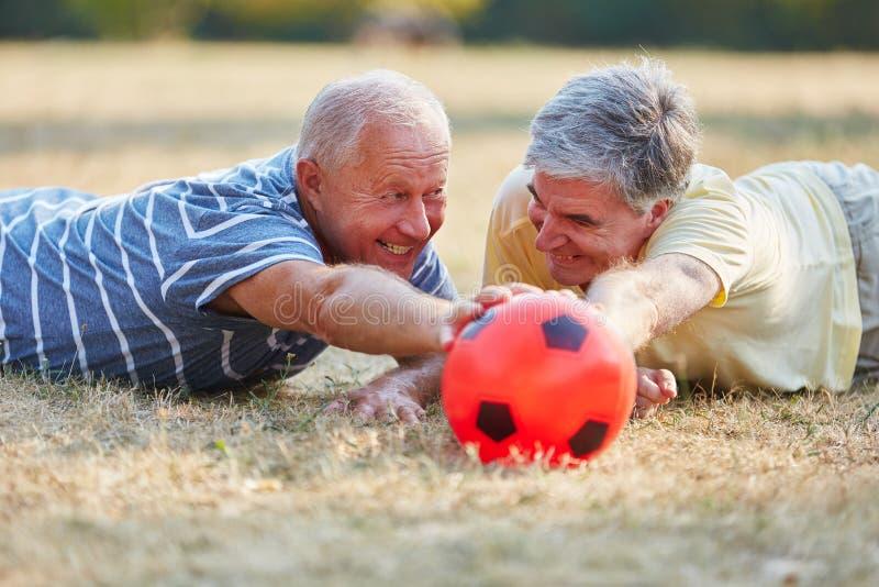 Dwa seniora dosięga piłkę podczas meczu piłkarskiego zdjęcia royalty free