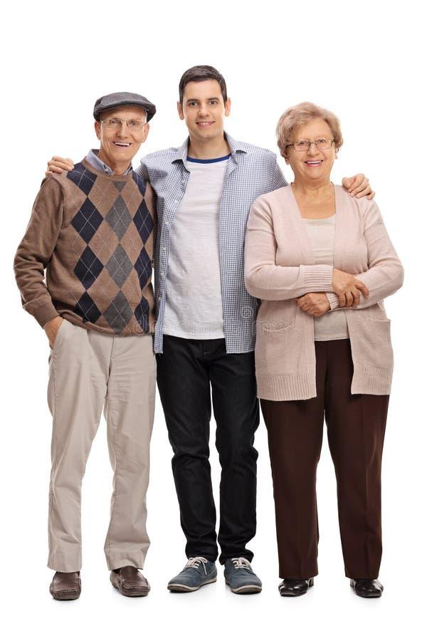 Dwa seniora i młody człowiek pozuje wpólnie zdjęcia royalty free