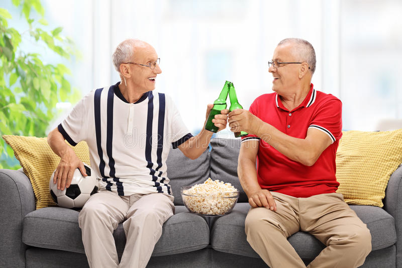 Dwa seniora ogląda piłkę nożną i pije piwo fotografia stock
