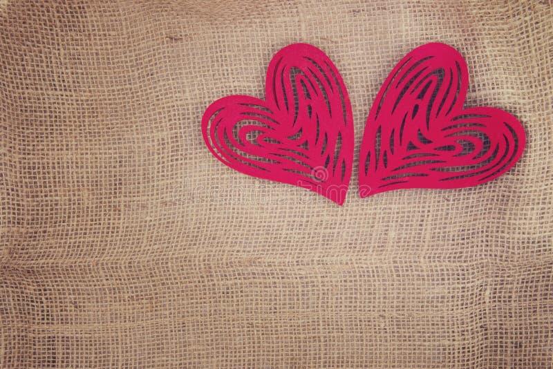 Dwa serca popierają kogoś popierają kogoś na burlap - obok - zdjęcie royalty free